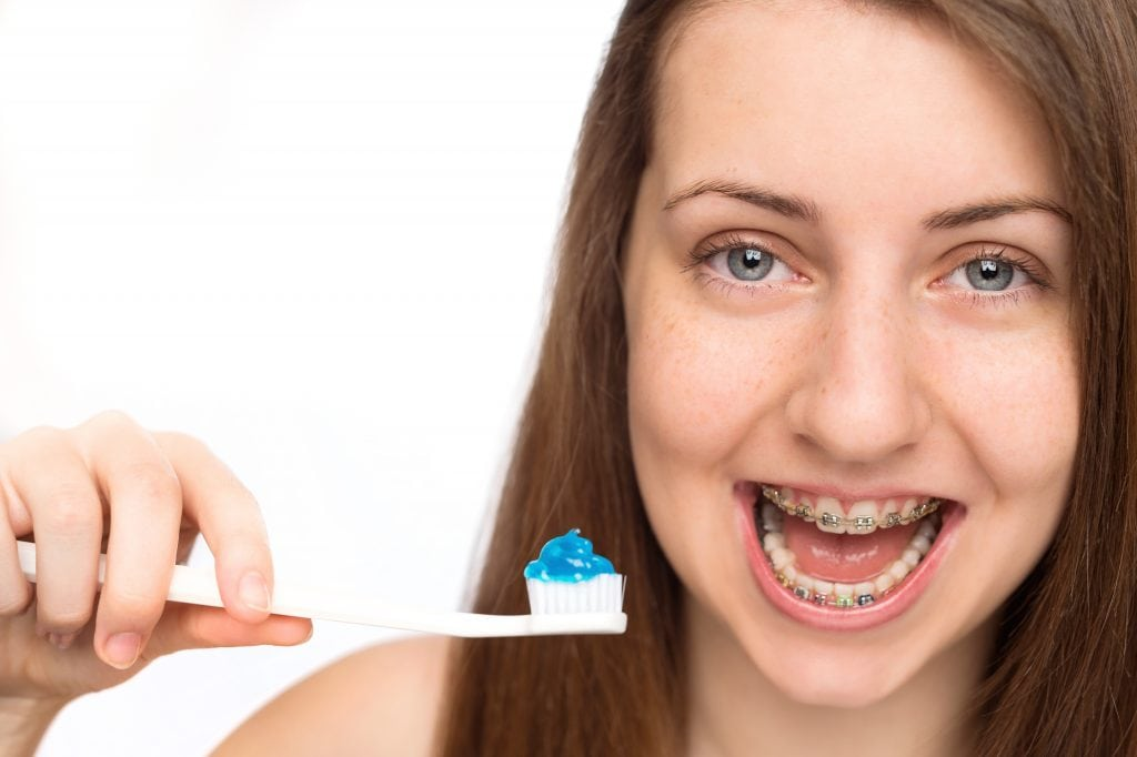 Happy girl with braces holding toothbrush morning hygiene isolated